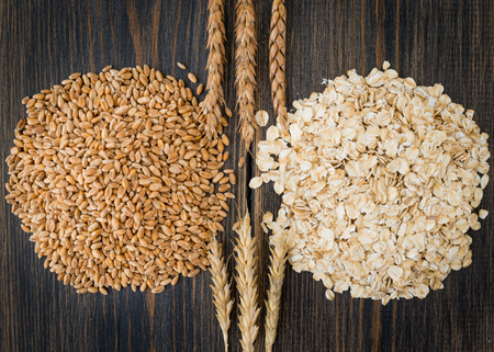 Dry oat ears or bunting cereals and raw oat flakes or oatmeal with oat spikes or spikelets herbs on black rustic wooden background top view close-up. Фото со стока
