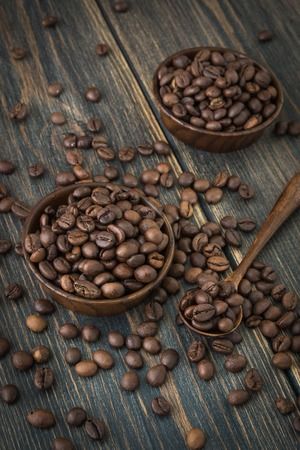 A wooden plate of roasted arabica coffee beans on a dark wooden background closeup