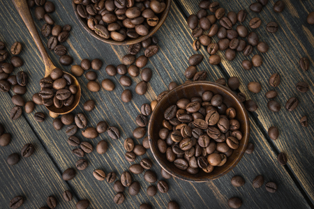 Two wooden plates of roasted coffee beans on a black wooden background top view