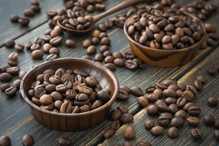 Wooden plates of black coffee grains on a dark wooden background close-up Фото со стока