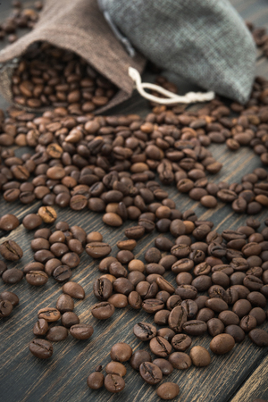 Two bags of roasted black coffee grains on a dark wooden background closeup