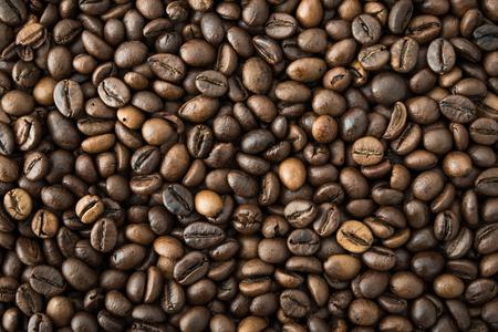 Roasted black coffee grains background top view Фото со стока