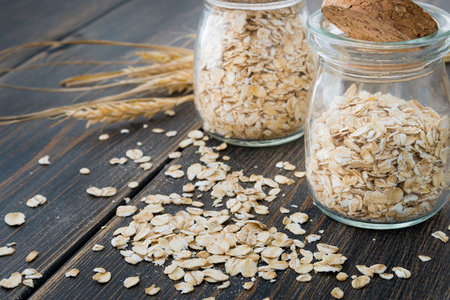 Oat flakes or oatmeal cereal in craft glass jars with oat spikes or spikelets on dark rustic wooden background close-up Фото со стока