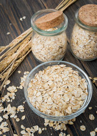 A glass plate of dry oat flakes or oat grains with oat spikes or spikelets on dark rustic wooden background Фото со стока