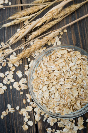 Dry oat flakes or bunting cereal in glass plate with oat spikes or spikelets on dark rustic wooden background top view close-up