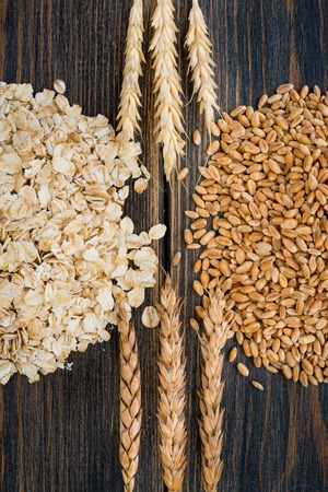 Dry rolled oats or bunting cereals and oatmeal with oat spikes or spikelets herbs on black rustic wooden background top view close-up