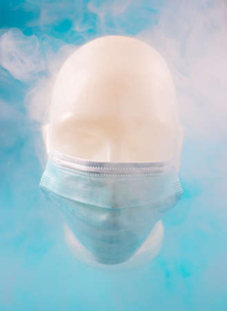 Minimal abstract composition background of a human face wearing a mask, covered in smoke, on a blue background. Global pandemic concept.