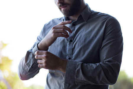 Attractive young businessman buttoning up his shirt and sleeves