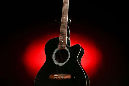 Acoustic guitar with red and black gradient background