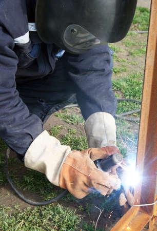 Welder welding a metal part wearing standard protection equipment.