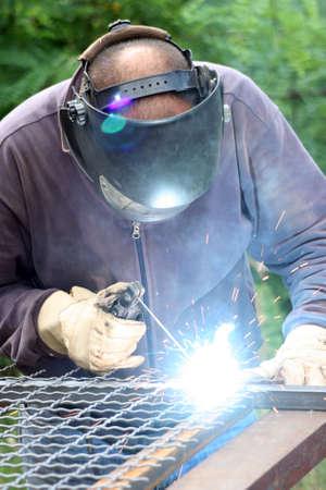 Welder welding  a metal part wearing standard protection equipment