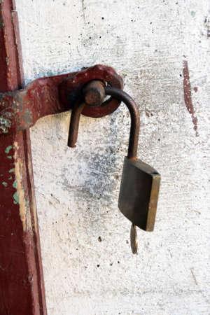 Unlocked padlock and key on a wall