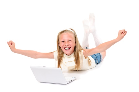 Happy and smiling little girl with laptop on white background isolated photo