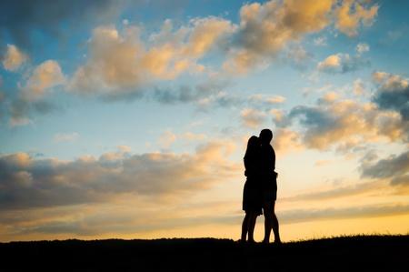 silueta masculina: Silueta de joven pareja al atardecer Foto de archivo