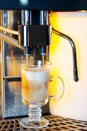 Making capuchino in coffee machine in bar photo