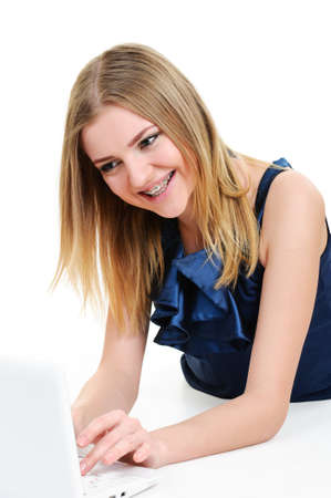 girl with braces working on laptop on white background  photo