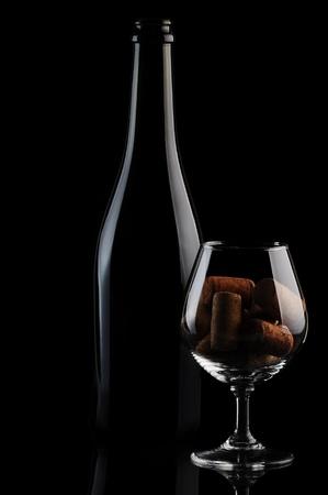 Cork in a glass and wine bottle on black background Stock Photo
