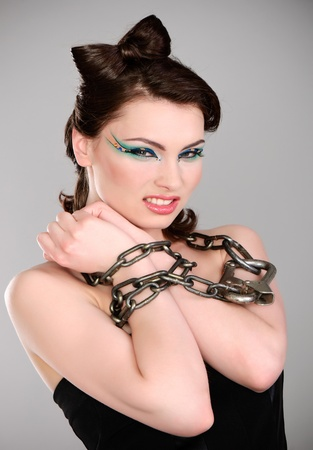 young brunette with chain and makeup studio shot photo