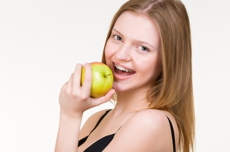 Beautiful young woman with brackets on teeth eating apple