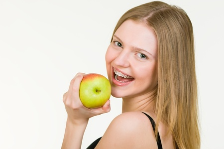 Beautiful young woman with brackets on teeth eating apple on white background
