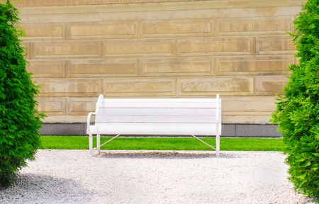 Empty wooden bench on the wall background a sunny day photo