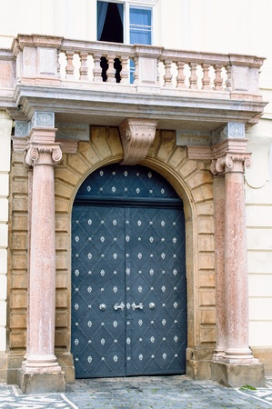Traditional medieval european door with columns and balcony on street Prague