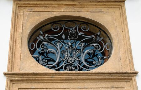 The beautiful forged on an oval window on street Prague Stock Photo - 14354698