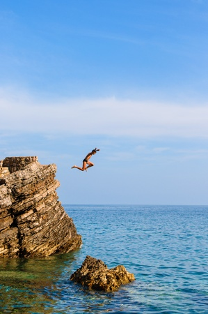 Boy Jumping Off Cliff Into Blue Water at sunset photo
