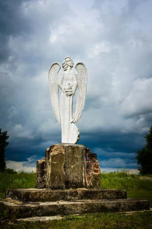 angel cemetery: wooden statue of an angel with a sword on a background of clouds