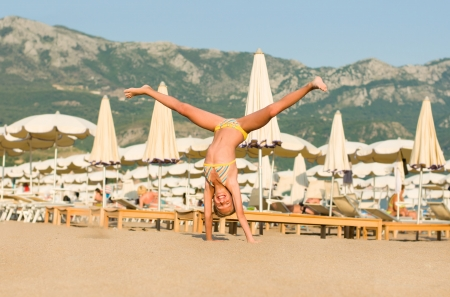 Beautiful happy girl somersault on the beach Montenegro