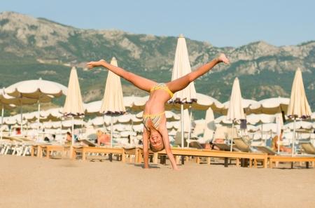 somersault: Beautiful happy girl somersault on the beach Montenegro