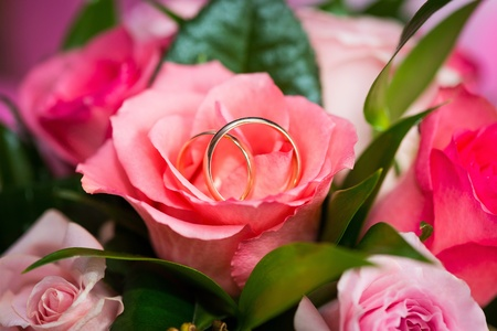 Two golden wedding rings on rose in bridal bouquet