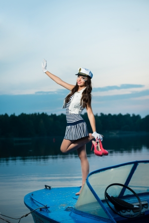 Young beautiful sailor woman on the boat at sunset photo