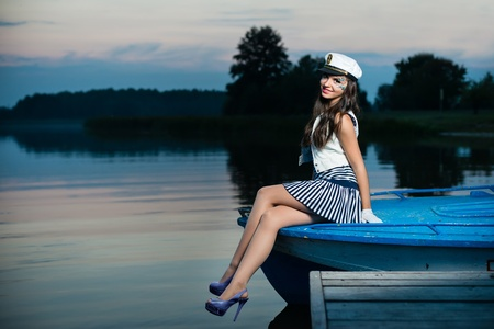 Young beautiful sailor woman sitting on the boat at sunset Stock Photo