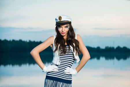 Young beautiful sailor woman on the boat at sunset