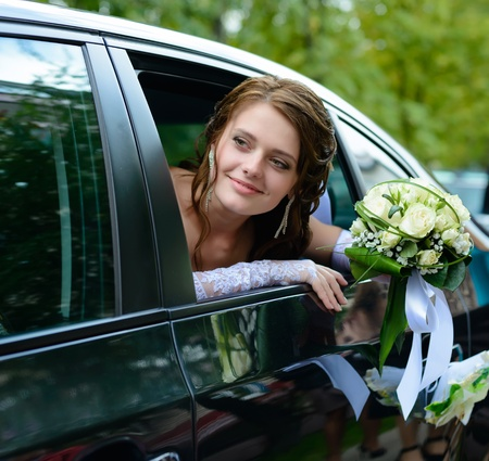 portrait of a pretty smiling bride in a car window photo
