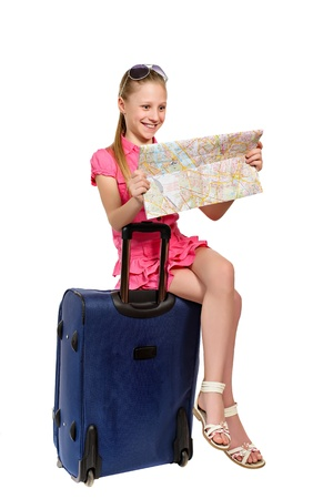 girl with map sitting on a suitcase isolared on white background photo