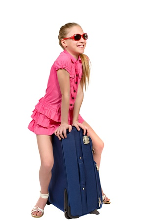 little girl surprised: girl with sunglasses sitting on a suitcase isolated on white background