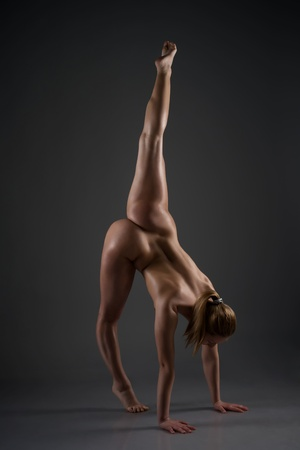 Naked female gymnast posing in studio Stock Photo