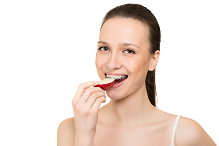Young woman with brackets on teeth eating apple isolated