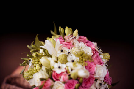 Two golden wedding rings on bridal bouquet