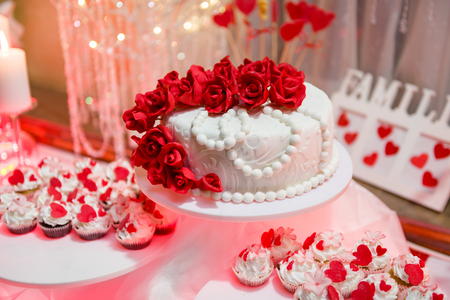 Beautiful wedding cake and cupcakes in decoration