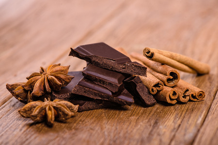 chocolate pieces, star anise and cinnamon sticks close up photo