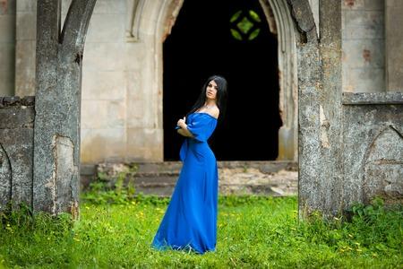 church ruins: Portrait Of Sensual Fashion Woman In Blue Dress in church ruins Stock Photo