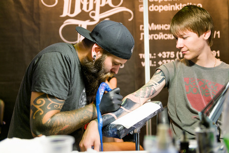 tatouage: Minsk, Bi�lorussie - 19 septembre 2015: tatoueur professionnel faisant tatouage sur la main du client. La 2�me Convention internationale de tatouage �ditoriale