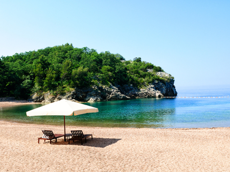 sheltered: Vacation concept. Two chairs under a white umbrella on a sandy beach in sheltered bay. Mediterranean sea
