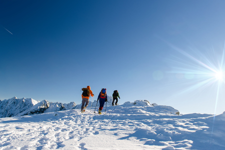 Group hikers in winter mountains, beautiful landscape and blue sky Stock Photo