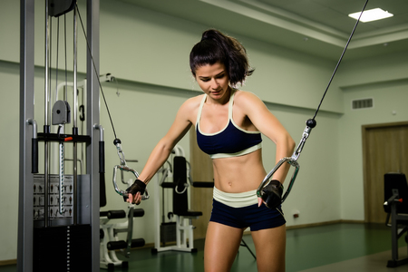 Young pretty woman pumping up muscles with training apparatus in fitness club Stock Photo