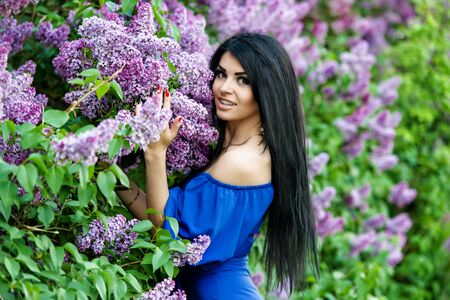 beautiful flowers: Beautiful smiling young woman with lilac flowers Stock Photo