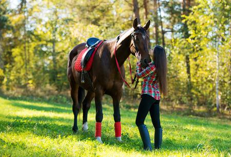 yegua: joven y bella mujer de pelo largo con un caballo al aire libre
